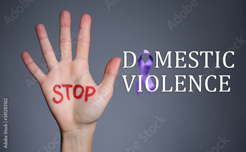 Fototapeta Female hand with text STOP DOMESTIC VIOLENCE on grey background obraz