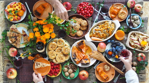 Fototapeta Country style. Thanksgiving table. Lots of food with red wine. The guests eat food with their hands over the set table. View from above. obraz