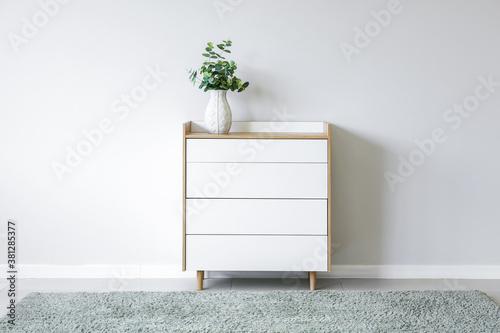 Fototapeta Modern chest of drawers near light wall in room obraz