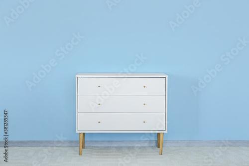 Fototapeta Modern chest of drawers near color wall in room obraz