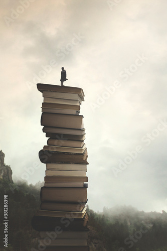 man successfully reaches the peak of knowledge by  climbing a stack of books Wallpaper Mural