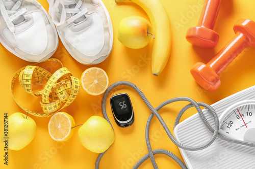 Fotografie, Obraz Fruits, scales, measuring tape, sports equipment and glucometer on color background