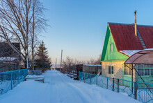 Street In Country Village Covered With Snow And Left For The Winter Brick Cottage House On Wintery Evening At Sunset. Russian Dacha Concept