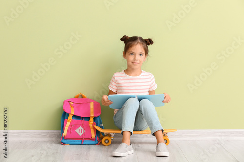 Fotografía Little schoolgirl with skateboard and notebook sitting near color wall