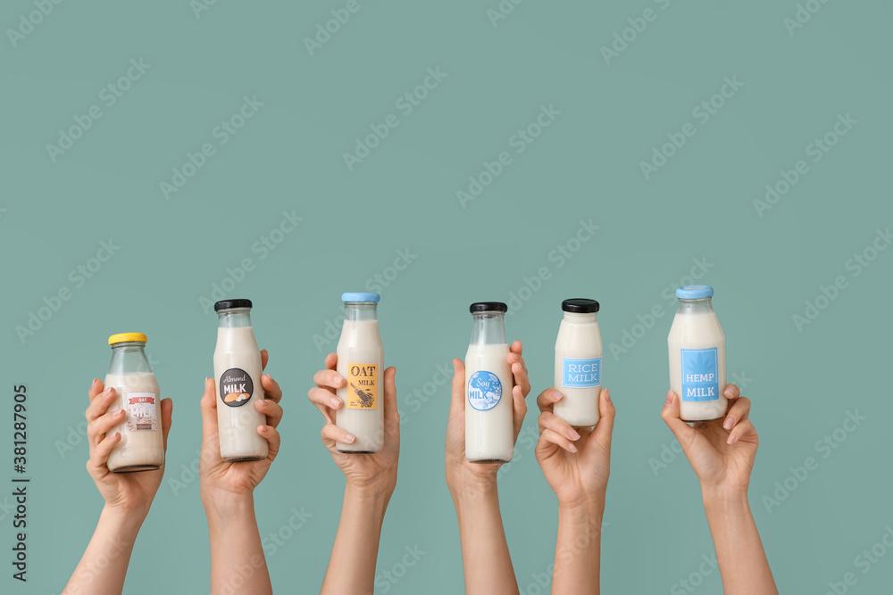 Fototapeta Female hands with bottles of vegan milk on color background