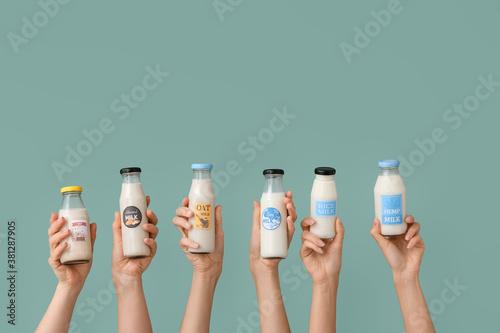Fotografie, Obraz Female hands with bottles of vegan milk on color background