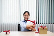 Asian woman holding a gift box Glad to be the giver of surprise with excitement, joy and smiles on the holidays, Christmas, birthdays or Valentine's Day concept