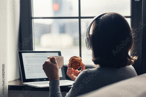 Obraz Back view of lonely woman enjoying having breakfast with cup of coffee and croissant, listenning music in headphones working on laptop sitting near window in cafe. - fototapety do salonu