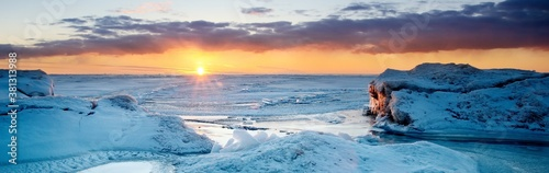 Obraz na plátne Picturesque panoramic scenery of the snowy Baltic sea shore at sunset,ice fragments close-up