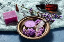 Aromathreapy Concept. Essential Oil, Infused Soap, Scented Candle, Incense Cone, Perfume Vial With Lavender And Vervain Flowers On A Blue Background