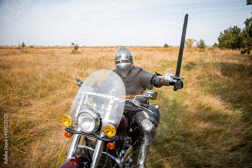 Fotomural A medieval knight in chainmail and a helmet with a sword in his hands sits on a motorcycle