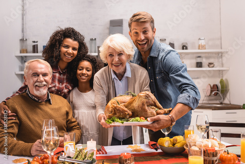 Selective focus of multiethnic family holding turkey and looking at camera during thanksgiving