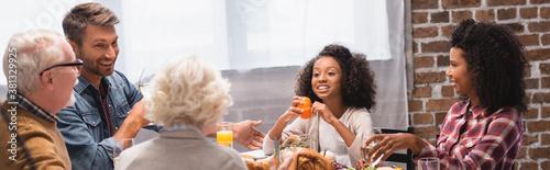 Fototapeta Panoramic shot of multicultural family sitting near tasty turkey on table during thanksgiving dinner obraz