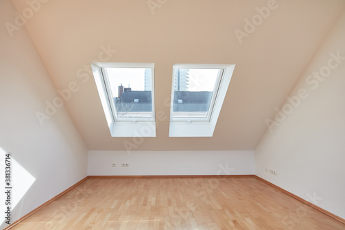 Fototapeta Empty room with window and sloping ceiling in the attic obraz