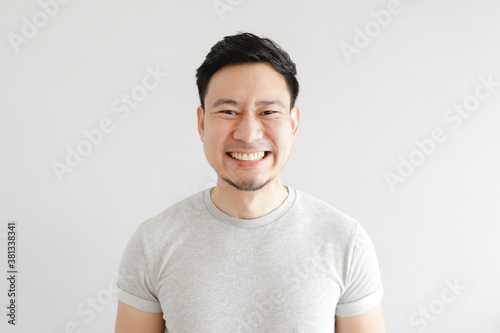 Fototapeta Smile face of happy Asian man wear grey t-shirt and on grey background. obraz