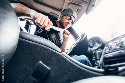 Fototapeta Inside view of a powerful car - a man with stubble in a hat and sunglasses faste