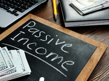 Passive Income Inscription On The Board And A Bundle Of Bills.