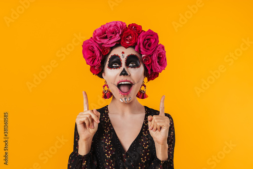 Fotografie, Obraz Photo of excited girl in halloween makeup pointing fingers upward