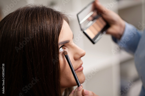 Obraz na plátně Professional makeup artist working with beautiful young woman