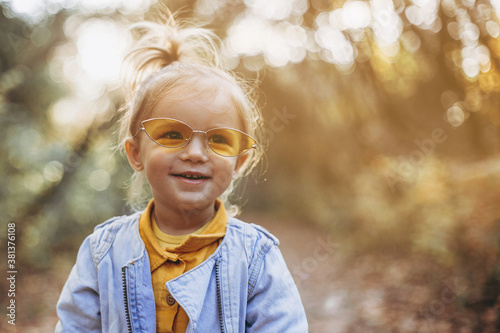 little pretty girl posing for a photo while walking with her parents in autumn park, an infinitely happy and joyful child, selective focus, noise effect
