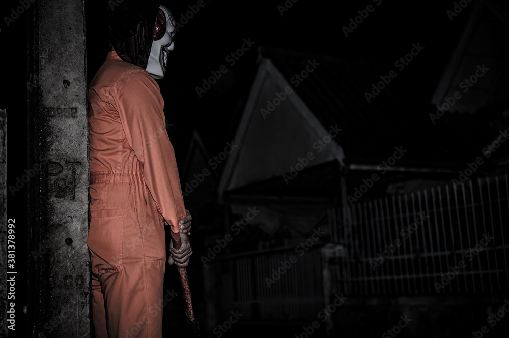 Fototapeta Asian handsome man wear clown mask with weapon at the night scene,Halloween festival concept,Horror scary photo of a killer in orange cloth