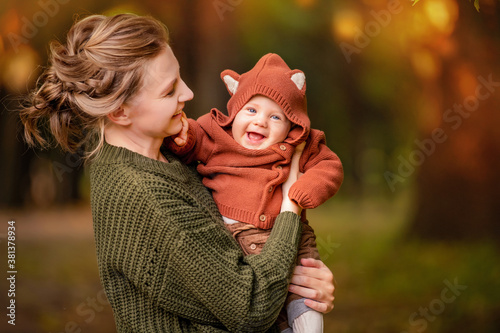 Happy mom holds a laughing baby in her arms for walk in autumn park Canvas-taulu