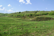 A Field With An Embankment. In The Background Is A Hill With Small, Rural Houses. Sunny, Clear Day.