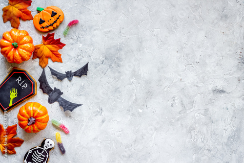 Halloween decoration concept with pumpkins, cookies and autumn leaves, top view