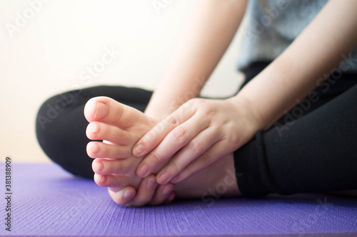 Photo Foot pain - Young female massaging her painful foot after sport workout indoors while sitting on stretching mat
