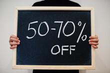 50-70 Percents Written On Blackboard. Black Friday Concept. Boy Hold Board.