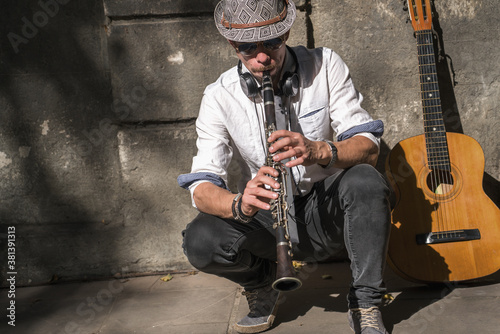 Portrait of caucasian man playing the clarinet outdoors Wallpaper Mural