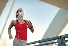 Below View Of Female Runner Jogging With Protective Face Mask Outdoors.