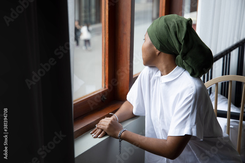Fototapeta Portrait of sad African young woman cancer patient fighting with the sickness, wearing head scarf after suffering serious hair loss side effect due to chemotherapy, concept of cancer awareness obraz