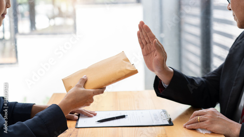 Photo Confident businessman manager rejecting an offer of money to agreement contract from partner or refusing to take bribe, Bribery and corruption concept