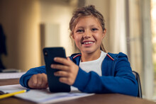 Authentic Shot Of Little Girl Pupil Is Sitting At Desk And Using Smartphone While Doing Homework To Prepare For School Day And Smiling In Camera In Her Room At Home.