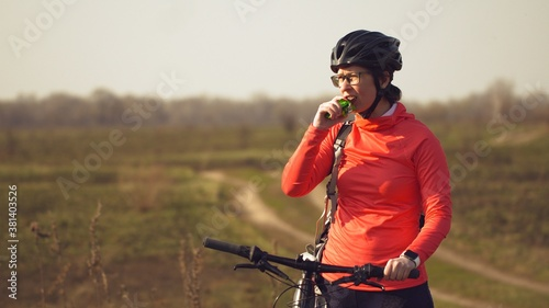 Fototapeta Athletic Caucasian woman eats protein bar ride on mountain bike on nature. Young sporty woman athlete in helmet resting while biting nutritional bar. Fitness woman eating energy snack outdoor obraz