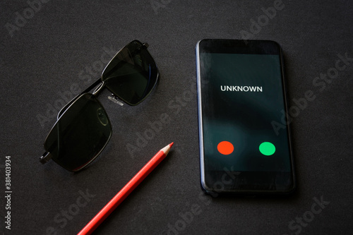 Vászonkép A smartphone with an unknown call lies on a black surface next to a red pencil and sunglasses