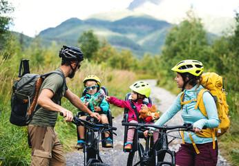 Obitelj s malom djecom biciklirajući na otvorenom u ljetnoj prirodi, odmarajući se.