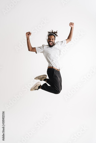 Fotografie, Obraz Photo of jumping while dancing african american guy in headphones jumping while