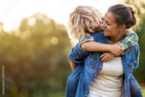 Fototapeta Mother and son having fun outdoors