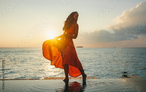 Woman at a beach resort during sunset - 381417558