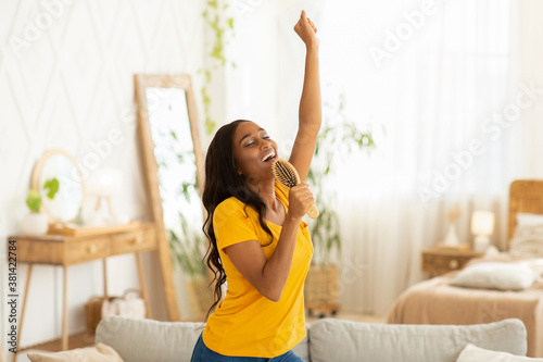 Fotografie, Obraz Cheerful black woman with hairbrush as mic singing her favorite song and dancing