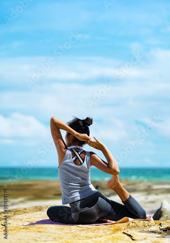 A beautiful woman doing yoga on the rocks at the beachside. Canvas Print
