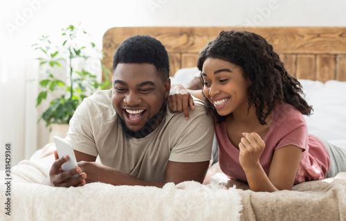 Fototapeta Happy black couple celebrating success, holding smartphone obraz