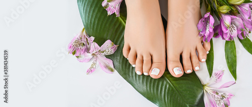Leinwand Poster Beautiful perfect female skin legs feet top view with tropical flowers and green palm leaf