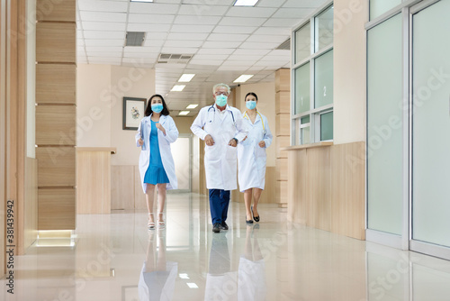 Photo Three doctors with mask running in a lobby