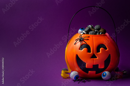 Fototapeta Jack-o-lantern bag full of candy on a purple background with copy space, horizontal obraz