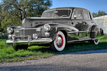 Front View Of Classic, Vintage, Luxury Car In Rural Setting With Whitewall Tires, Red Wheels, Chrome Hubcaps, Bumper, Grill, Fog Lights, And Rounded Hood