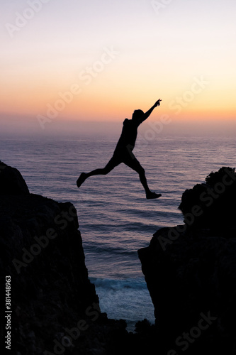 Photo Silhouette of a young man in the top of a cliff jumping between stones with the sea in the middle and the background