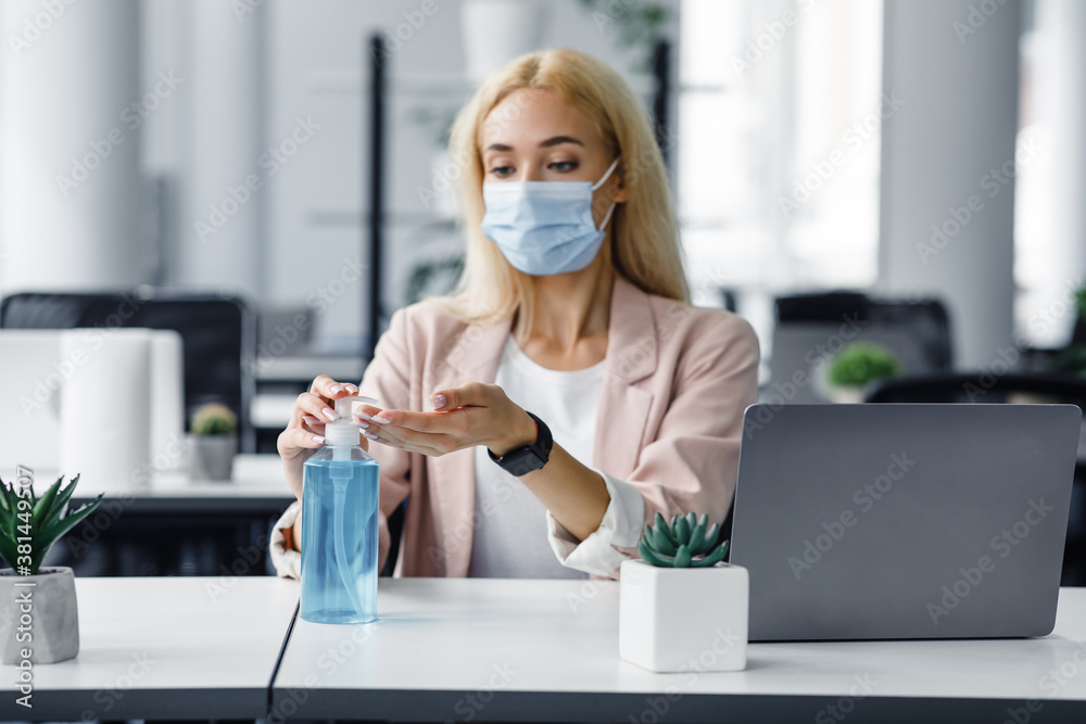 Fototapeta Safety and health protection at work in office. Millennial woman in protective mask with smart watch uses antiseptic at workplace with laptop for hand disinfection